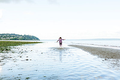 Wide angle view of a child running through shallow water by the beach - p1166m2289950 by Cavan Images