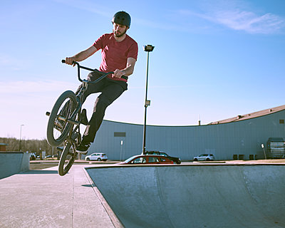 Bmx rider mid air coming out of ramp in skatepark on warm summer day, Montreal, Quebec, Canada - p1362m2117384 by Charles Knox