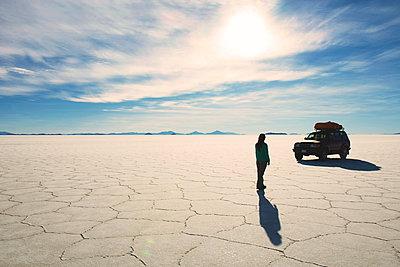 Bolivia, Potosi, Woman walking towards her 4x4 in Uyuni salt flats - p300m1068951f by Gemma Ferrando
