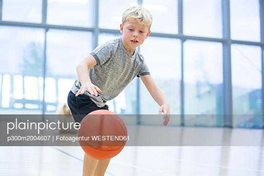 Schoolboy playing basketball in gym class - p300m2004607 von Fotoagentur WESTEND61