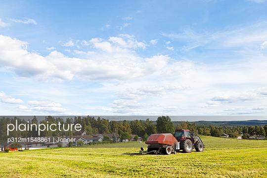 plainpicture | Photo library for authentic images - plainpicture p312m1548861 - Rural scene of tractor in f... - plainpicture/Johner