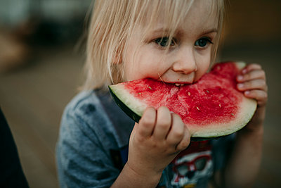 Cute boy eating watermelon at porch - p1166m1489119 by Cavan Images