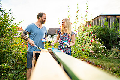 Smiling couple looking at each other while painting wooden planks in garden - p300m2264556 by Annika List