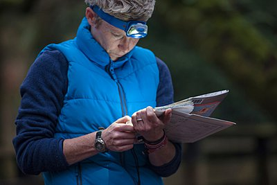 Mid adult woman studying map - p429m1021830f by Colin Hawkins