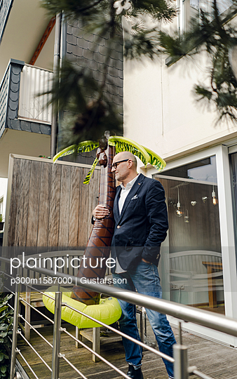 Senior businessman standing in his garden, holding a rubber palm, dreaming of vacations - p300m1587000 von Gustafsson