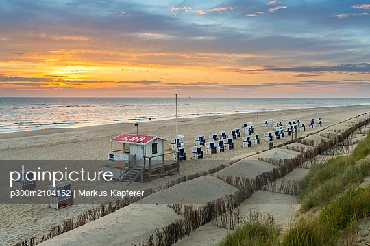 Germany, Sylt, North Sea, sandy beach with hooded beach chairs in sunset - p300m2104152 by Markus Kapferer