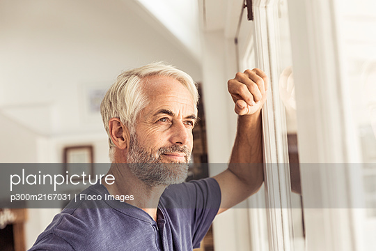 Portrait of mature man looking out of window - p300m2167031 by Floco Images