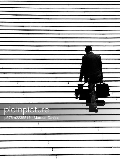 Businessman ascending steps - p378m2235519 by Marcus Davies