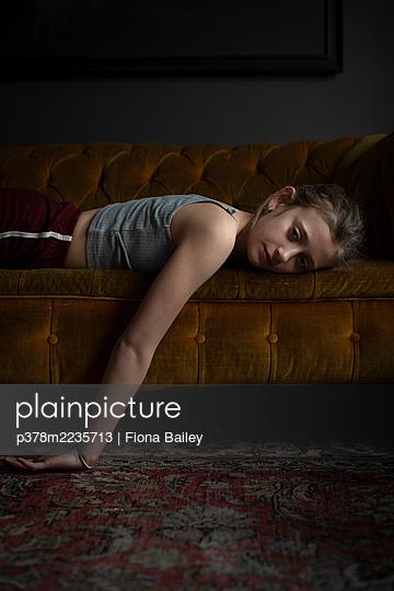 Girl lying on sofa - p378m2235713 by Fiona Bailey