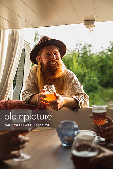 Bearded man with beer glass talking with friends in motor home - p426m2296268 by Maskot