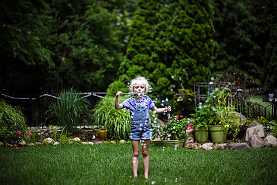 Cute girl blowing bubbles while standing on grassy field in park - p1166m2105976 by Cavan Images