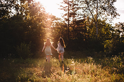Back view of girlfriends holding hands while running in summer forest - p1166m2212473 by Cavan Images