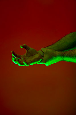 Green illuminated hands against red background - p1248m2260663 by miguel sobreira