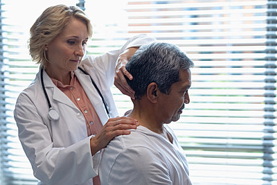 Female doctor examining male patient neck in hospital - p1315m2117799 by Wavebreak
