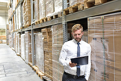 Businessman looking at clipboard in warehouse - p300m1499608 by lyzs
