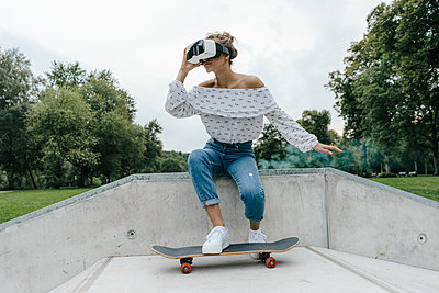 Young woman with skateboard wearing VR glasses in a skatepark - p300m1536249 by Kniel Synnatzschke