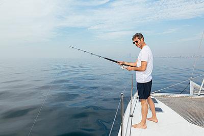Mature man standing on catamaran, fishing - p300m2012486 by Bonninstudio
