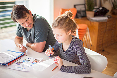 Father helping daughter with homework - p312m1471000 by Christina Strehlow