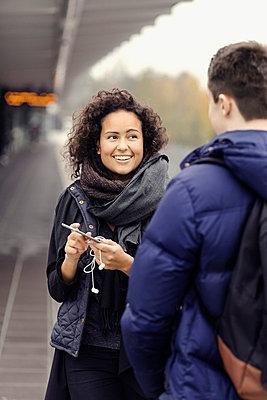 Happy couple using mobile phone on subway platform - p426m1003771f by Maskot