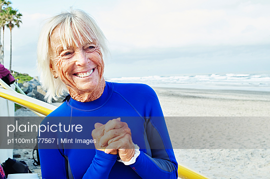 Smiling senior woman wearing a wetsuit, standing on a sandy beach. - p1100m1177567 by Mint Images