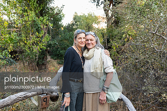An adult woman and her mother on a walkway through the trees at a safari camp - p1100m2300972 by Mint Images