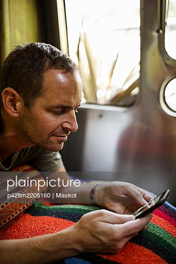 Mature man using phone in camper trailer - p426m2205160 by Maskot