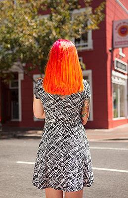 Frau mit schriller Haarfarbe am Straßenrand - p045m1362716 von Jasmin Sander