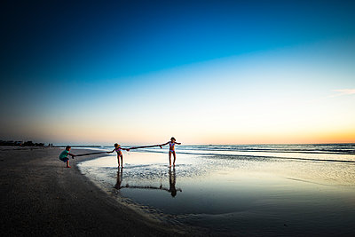 Siblings playing at beach against clear sky during sunset - p1166m1489100 by Cavan Images
