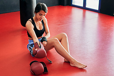 Young woman prepares to start Muay Thai training at a gym - p1166m2280865 by Cavan Images