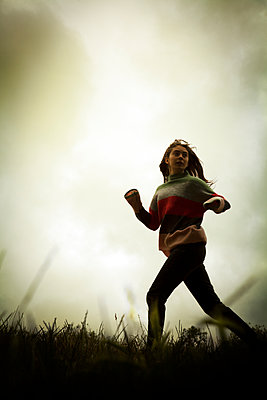 Young woman running on hill at twilight - p1248m2206138 by miguel sobreira