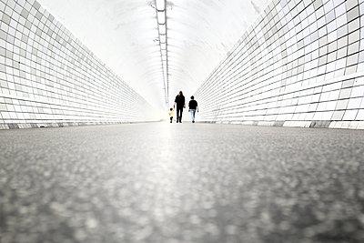 Family walking through pedestrian tunnel  - p1258m1165810 by Peter Hamel