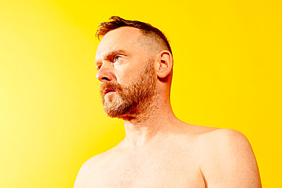 Red-haired man in front of yellow background, portrait - p1267m2272508 by Jörg Meier