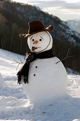 Snowman on mountainside wearing hat and scarf - p429m911540f by WALTER ZERLA