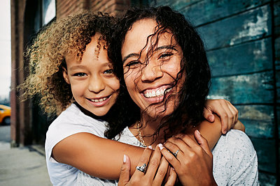 Mixed race mother and daughter hugging outdoors - p555m1410420 by Peathegee Inc