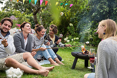 Friends roasting marshmallows at garden party - p788m1165406 by Lisa Krechting