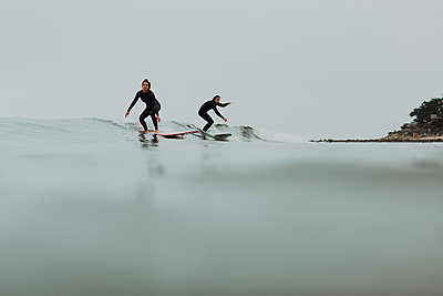 Young surfer couple surfing on calm misty sea, Ventura, California, USA - p924m2068287 by Peter Amend
