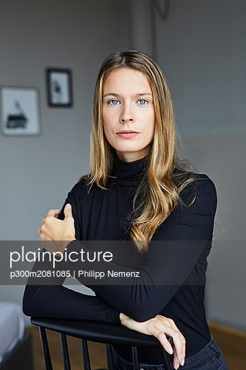 Portrait of young woman wearing black turtleneck sitting on chair - p300m2081085 by Philipp Nemenz