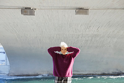 Portrait of woman with hands covering ears standing under city bridge - p1192m1031671f by Hero Images