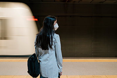 Female passenger waiting for her train at metro station during pandemic - p300m2240324 by Ezequiel Giménez