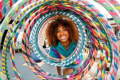 Portrait of smiling black woman behind hoops - p555m1521433 by Peathegee Inc