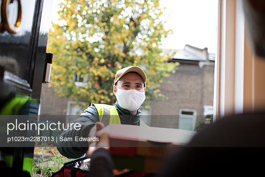 Delivery man in face mask delivering pizza at front door - p1023m2287013 by Sam Edwards