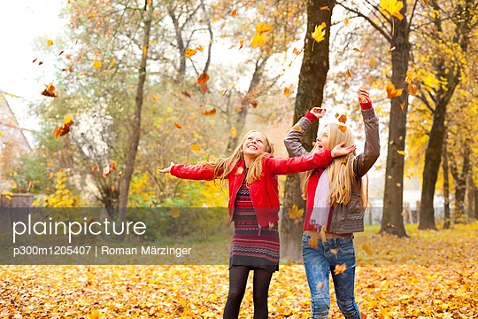 Two happy girls throwing autumn leaves in the air - p300m1205407 by Roman Märzinger