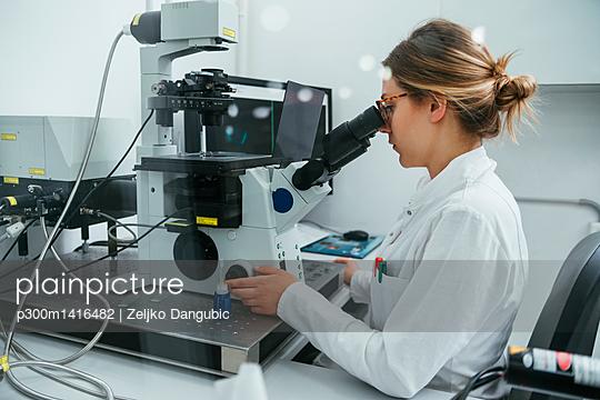 Laboratory technician using microscope in lab - p300m1416482 by Zeljko Dangubic