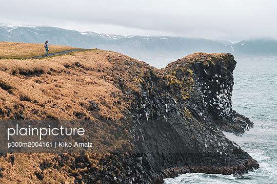 Iceland, young hiker looking at coast - p300m2004161 von Kike Arnaiz