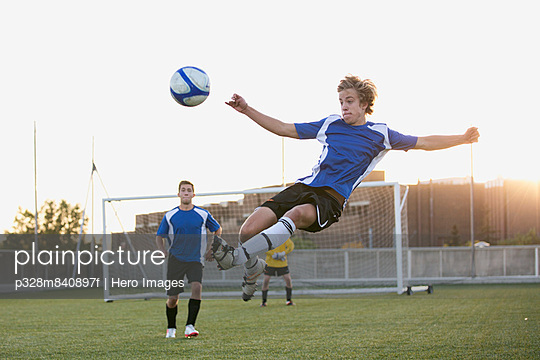 Soccer player in mid-air kicking ball.