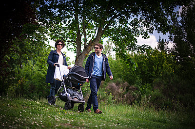 Young couple with stroller in nature - p1007m1183436 by Tilby Vattard