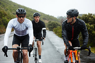Male cyclists cycling on wet road - p1023m1584015 by Richard Johnson