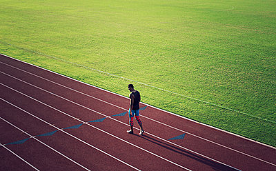 High angle view of male athlete walking on running tracks - p1166m1088141f by John Trice