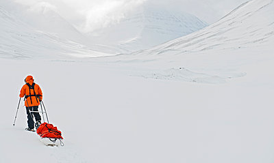 Woman dragging expedition sled in winter landscape - p1166m2268871 by Cavan Images