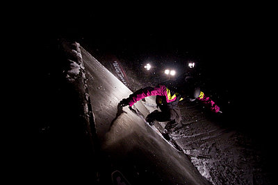 A snowboarder rides on a wallride in the terrain park at night. - p1424m1501280 by Noah Couser